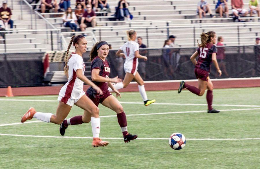 Junior defender Madison Kaufmann moves the ball forward as a Loyola University - Chicago defender applies pressure Sunday at home.