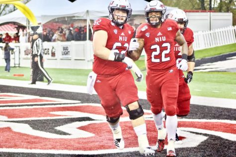 Christopher Perez Jr. (left), senior offensive lineman, and Tre Harbison, redshirt junior running back, celebrate a touchdown during NIU's 49-0 victory over Akron at Huskie Stadium.