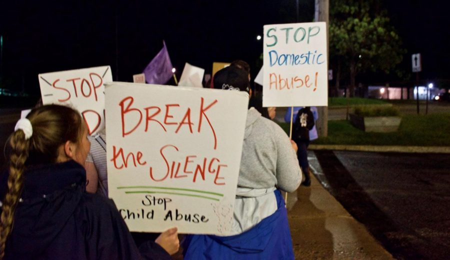 Students marching and holding signs around campus Thursday night during Take Back Night.
