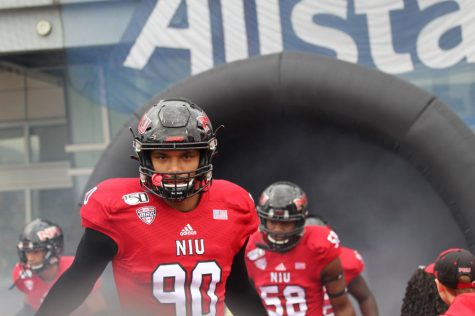 Caleb Wright, redshirt first-year defensive tackle, rushes out of the tunnel Oct. 5 before kick off against Ball State University at Huskie Stadium.