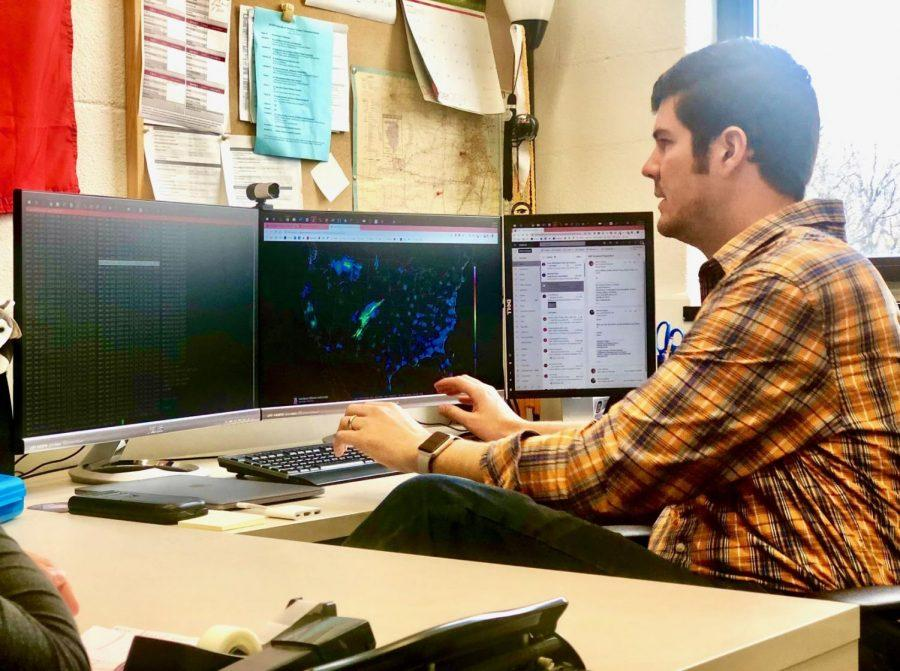Victor Gensini, assistant professor in the department of geographic and atmospheric sciences, navigates weather maps and observation data Oct. 28 in his office.