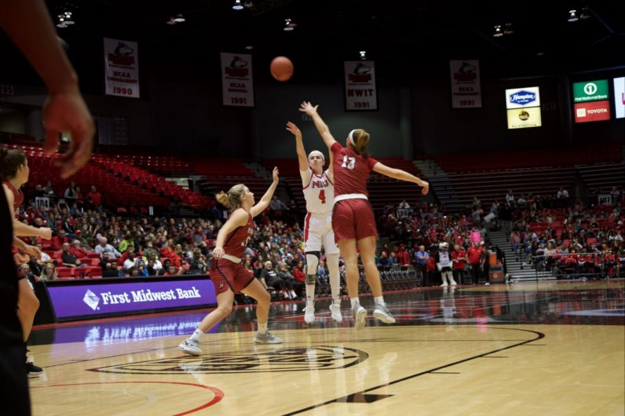 Redshirt+senior+forward+Courtney+Woods+shoots+over+two+Harvard+University+opponents+Nov.+5+during+NIU%27s+loss+to+the+Crimson+59-53+at+the+Convocation+Center.