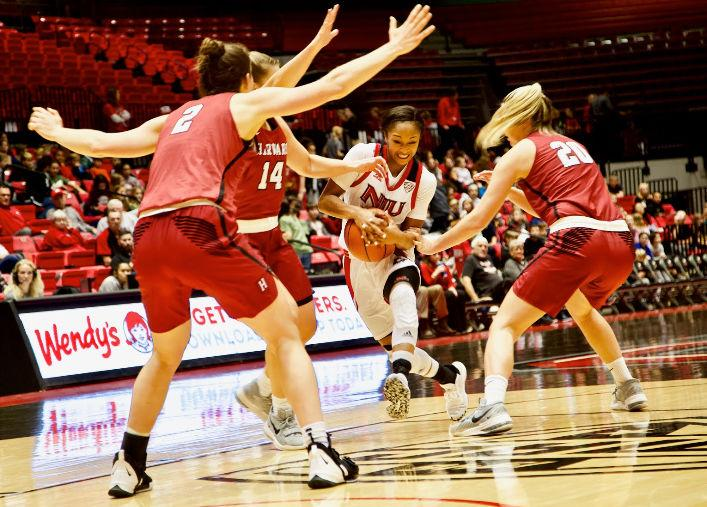 Senior guard Myia Starks charges through three Crimson defenders Tuesday in the Huskies' season opener. The team lost 59-53 at the Convocation Center.