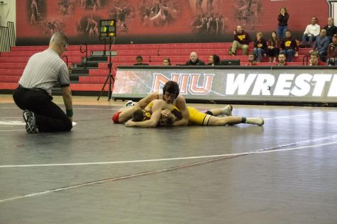 Redshirt first-year Anthony Gibson (top) attempts to pin his opponent Jan. 5 during NIU