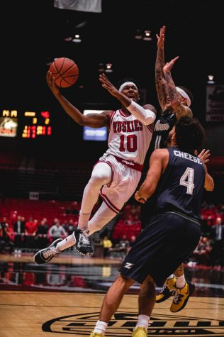 Senior Eugene German (center) rises into the air, taking contact from an Akron defender on a layup attempt during NIU