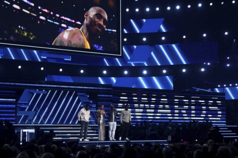Nathan Morris, from left, Wanya Morris, Shawn Stockman, of Boyz II Men, and Alicia Keys, second left, sing a tribute in honor of the late Kobe Bryant, seen on screen, at the 62nd annual Grammy Awards Sunday in Los Angeles.