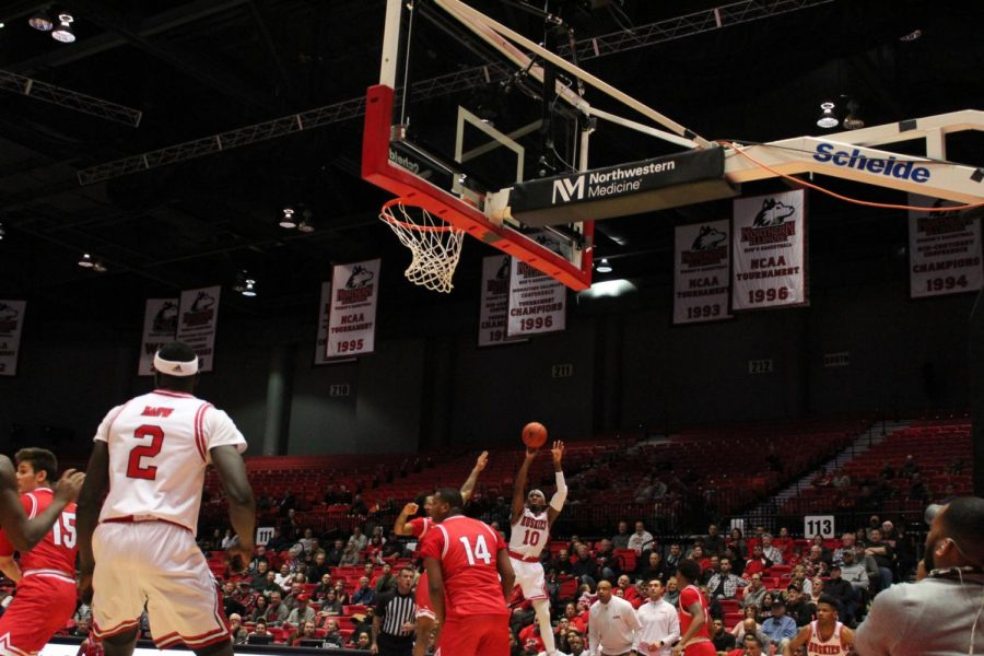 Senior Eugene German (10, center)shoots over a RedHawk defender Feb. 1 during NIU's 70-55 win over the Miami University-Ohio RedHawks at the Convocation Center.