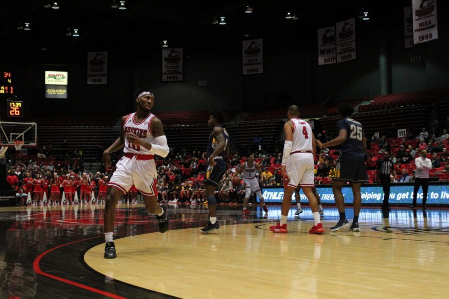 Senior Eugene German (center) runs to the right corner after handing off the ball to a sophomore Trendon Hankerson (back right) Feb. 7 during NIU's 57-54 win over Kent State University at the Convocation Center.
