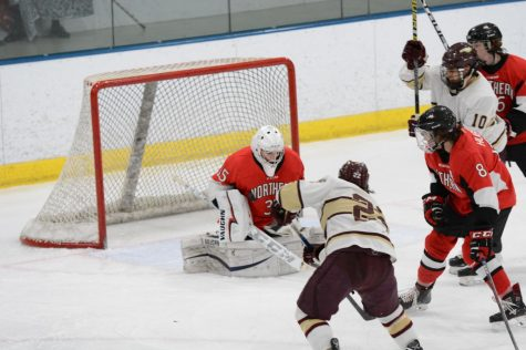 Sophomore goaltender Chad Dodero blocks a shot from a Robert Morris University player on Feb. 14 at Edge Ice Arena in Bensenville, Illinois.