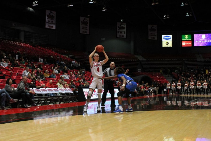 Redshirt senior Courtney Woods (left) looks to make a pass Feb. 1 during NIU's 64-63 win over the University at Buffalo at the Convocation Center.