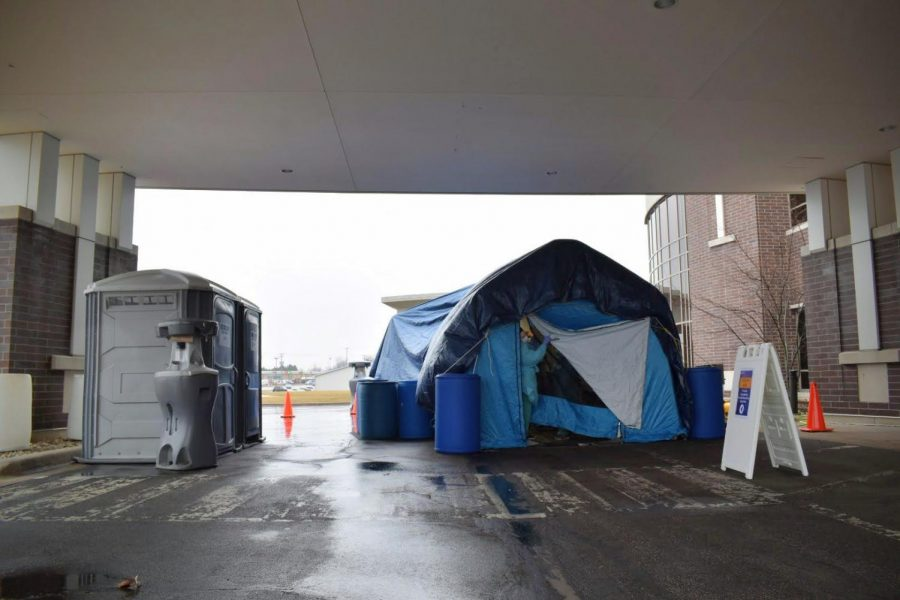 A+nurse+looks+out+of+the+flap+of+a+tarp+tent+erected+outside+Kishwaukee+Hospital%27s+emergency+wing%2C+1+Kish+Hospital+Drive.+A+nurse+on-site+said+they+are+currently+swabbing+patients+with+cold-+and+flu-like+symptoms.