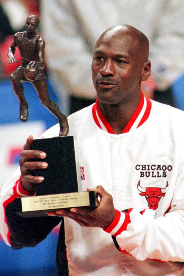 "In this May 19, 1998, file photo, Chicago Bulls' Michael Jordan looks at the MVP award presented to him before the Bulls-Indiana Pacers playoff game in Chicago. Jordan described his final NBA championship season with the Chicago Bulls as a ""trying year."" ""We were all trying to enjoy that year knowing it was coming to an end,"" Jordan told Good Morning America on Thursday, April 16, 2020. Jordan appeared on the show via video conference from his home in Florida to promote the ""The Last Dance,"" a 10-part documentary series focused on the final year of the 90′s Bulls dynasty that won six NBA titles in eight years. (AP Photo/Frank Polich, File)"