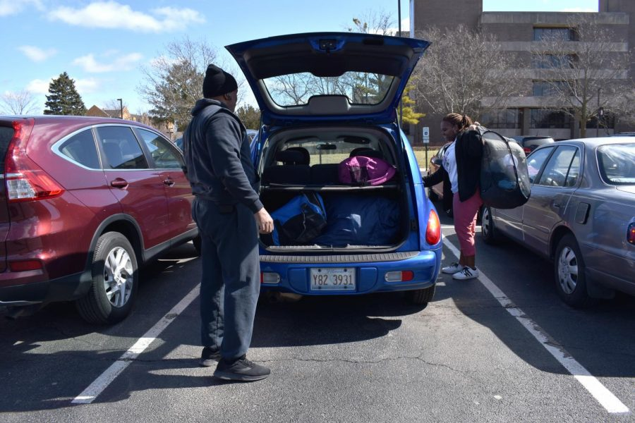 Jolan Lacy-Jones (right), sophomore performing arts major, loads her belongings into her father Kevin Jones' trunk in the visitor's lot. She's