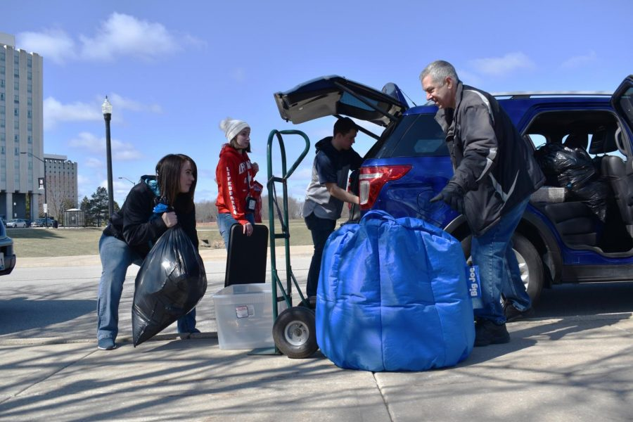 """Christy Thompson (left), of Roscoe, and Tim Terry (right), of Carol Stream, share a laugh as they help Breanna Terry (center left), first-year child development major, and Jason DuPont, first-year physics major, pack the car. Breanna said the early move-out is """"horrible,"""" and she"""