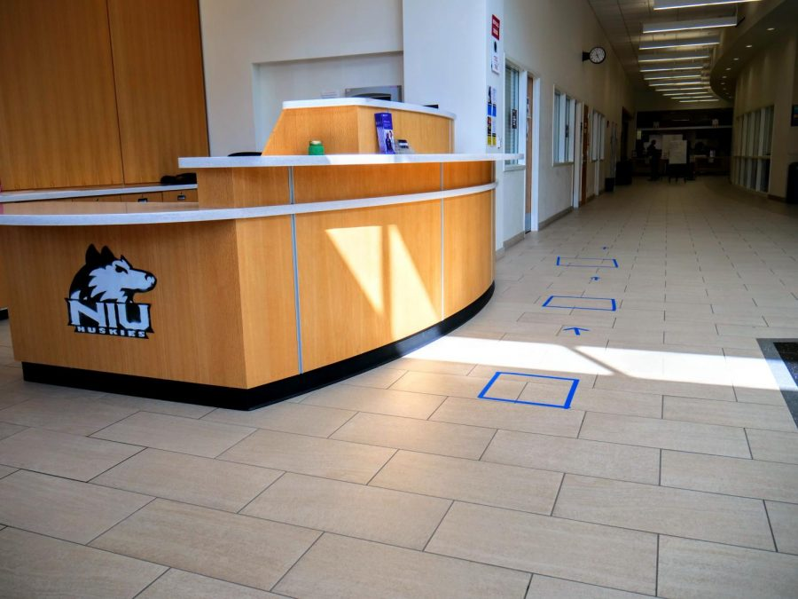 Squares of tape outline places to stand Monday for students to wait in line for their meals at New Hall Dining.