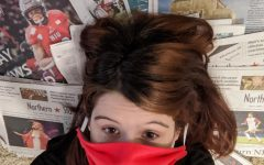 Editor in Chief Sam Malone lies on copies of the Northern Star with a mask covering her face.