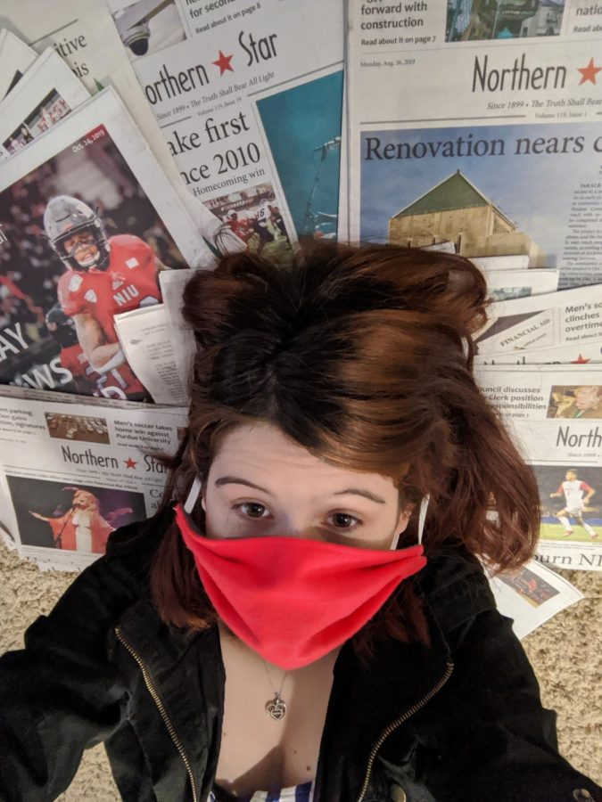 Editor+in+Chief+Sam+Malone+lies+on+copies+of+the+Northern+Star+with+a+mask+covering+her+face.