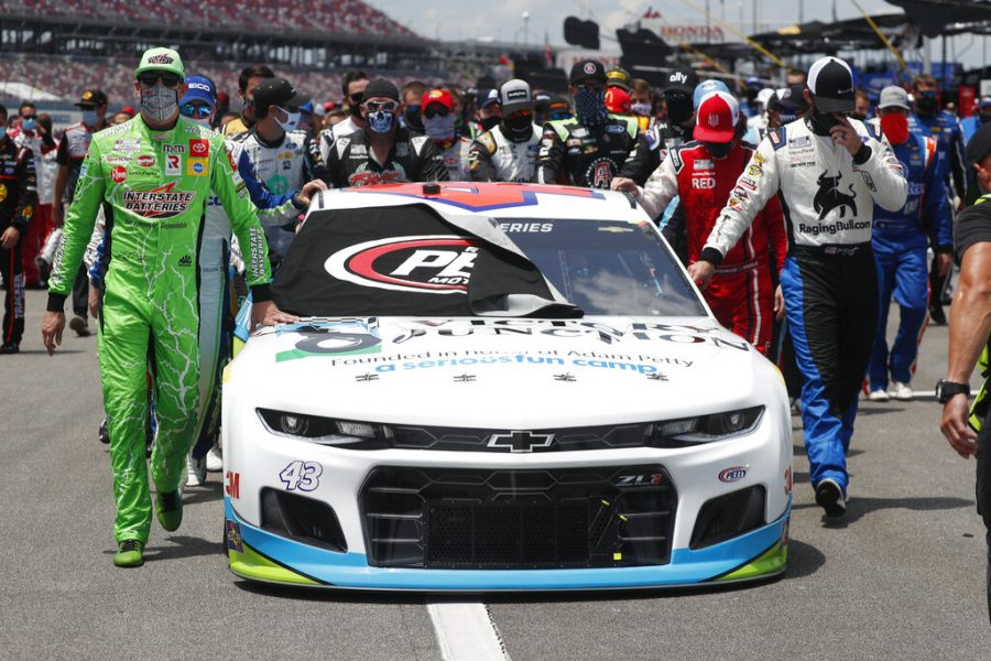 Nascar drivers Kyle Busch, left, and Corey LaJoie, right, join other drivers and crews as they push the car of Bubba Wallace to the front of the field prior to the start of the NASCAR Cup Series auto race at the Talladega Superspeedway in Talladega Ala., Monday June 22, 2020. In an extraordinary act of solidarity with NASCAR's only Black driver, dozens of drivers pushed the car belonging to Bubba Wallace to the front of the field before Monday's race as FBI agents nearby tried to find out who left a noose in his garage stall over the weekend.
