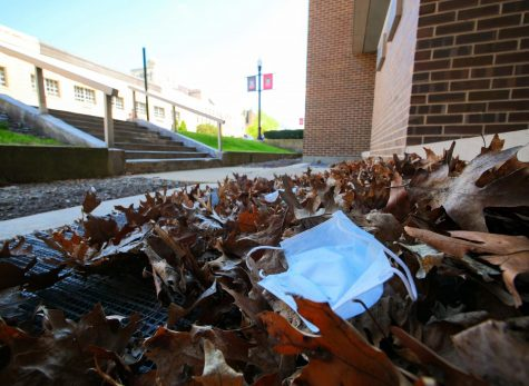 An abandoned face mask lays in a pile of leaves outside NIU