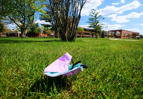 A cloth face covering lays in the grass outside DuSable Hall on Tuesday, May 12th.