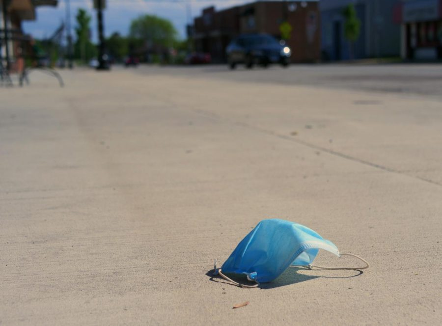 An abandoned disposable face mask lays on the sidewalk along Route 47 in downtown Elburn.