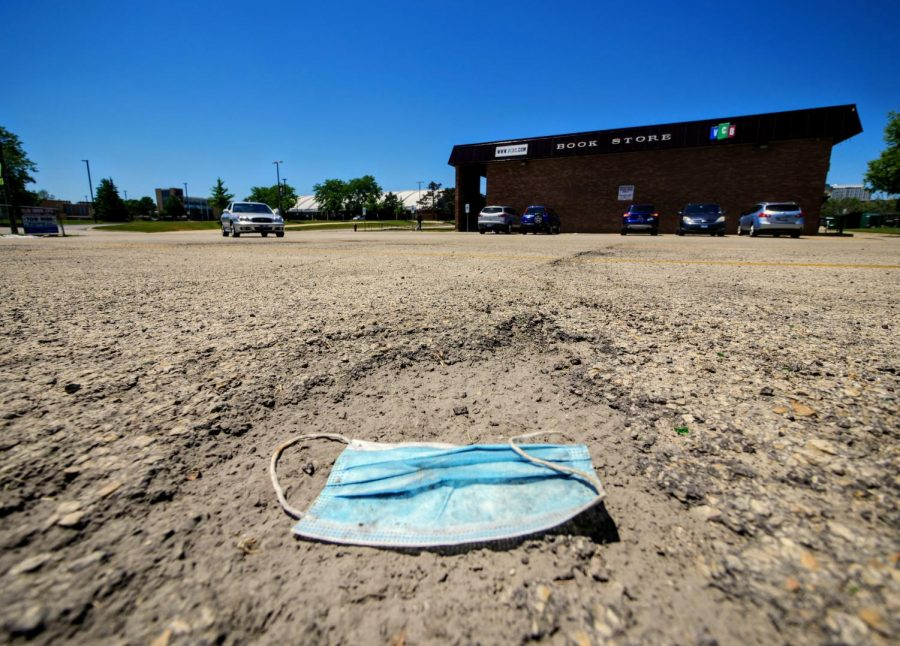 A wasted face mask lays in the parking lot outside of the Village Commons Bookstore in DeKalb on Friday, June 12th.