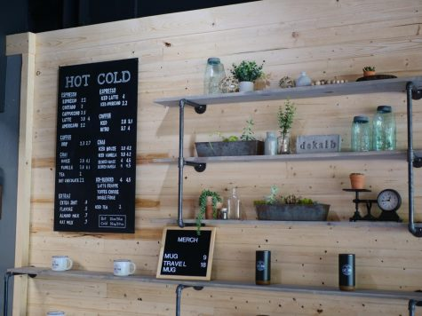 Merchandise sits on display shelves next to the menu in the new Cast Iron Coffee shop in DeKalb. Patrick Murphy