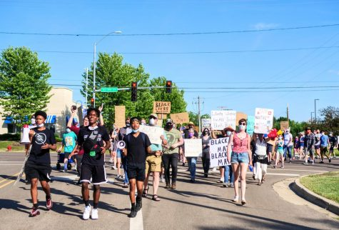 Andre Allen Jr., Anterrion Redd and Isaac Pierre lead a Juneteenth march down Sycamore Road in DeKalb on Friday.
