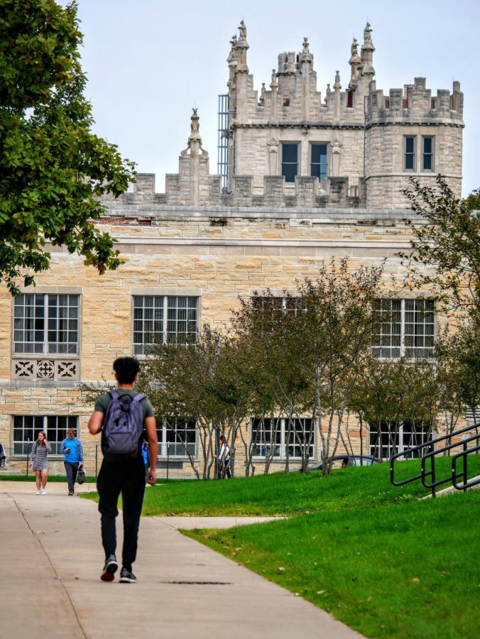 A student walks towards Swen Parson Hall.