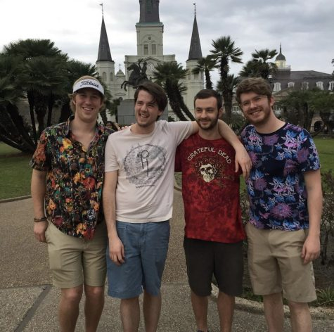 Four friends pose in front of New Orleans building