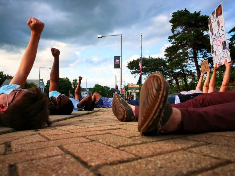 Black Lives Matter protesters raise their fists during a die-in demonstration in Memorial Park in DeKalb on Thursday.