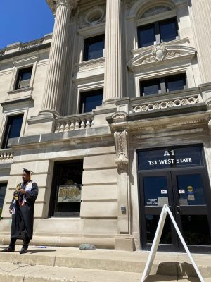 Advocacy and public communication major Roderic Moyer stands outside the DeKalb County Courthouse, 133 W. State St., Sycamore, wearing his cap and gown after instructor Michele Duffy's request for an order of protection against him was denied Tuesday.