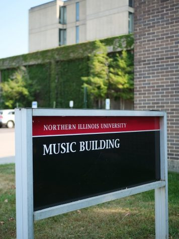 Music building sign stands in the grass along Lucinda Avenue in DeKalb.