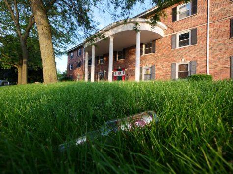 An empty beer bottle lies littered on the front lawn of a fraternity house on West Hillcrest Drive in DeKalb