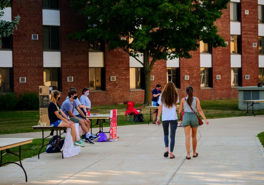 Students walk by tables near Neptune Hall during the involvement fair in August 2020.
