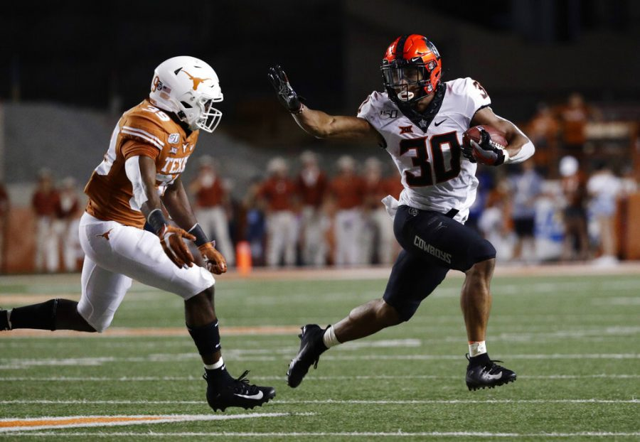 In this Sept. 21, 2019, file photo, Oklahoma State running back Chuba Hubbard (30) looks to fend off Texas defensive back Montrell Estell during the second half of an NCAA college football game in Austin, Texas. Oklahoma State plays Tulsa this week. The game was initially scheduled Sept. 12, but was postponed five days before that to allow the virus-affected Golden Hurricane more time to prepare for the season.