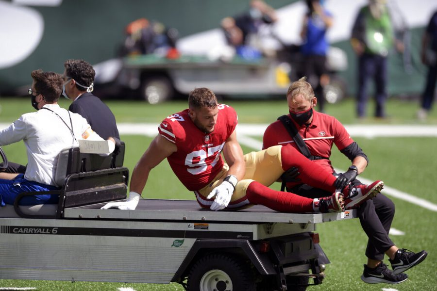 """San Francisco 49ers defensive end Nick Bosa (97) is driven off the field after being injured during the first half of an NFL football game against the New York Jets Sunday, Sept. 20, 2020, in East Rutherford, N.J. After losing four players to knee injuries last week against the New York Jets, the Niners complained about a """"sticky"""" new turf at MetLife Stadium and expressed some concern about returning to the same field a week later."""