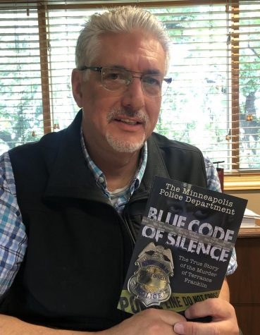 "Author Mike Padden holding his book ""The Minneapolis Police Department: Blue Code of Silence"""