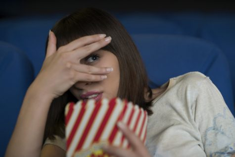 Young woman in the cinema, watching a scary movie, hiding her look with a hand and holding a box with popcorn