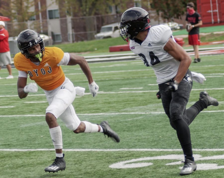 Redshirt junior cornerback Dillon Thomas (left) runs a drill  in practice Oct. 15 at Huskie Stadium. Thomas is wearing the B.Y.O.J. jersey awarded to the player who brings the most energy in practice.