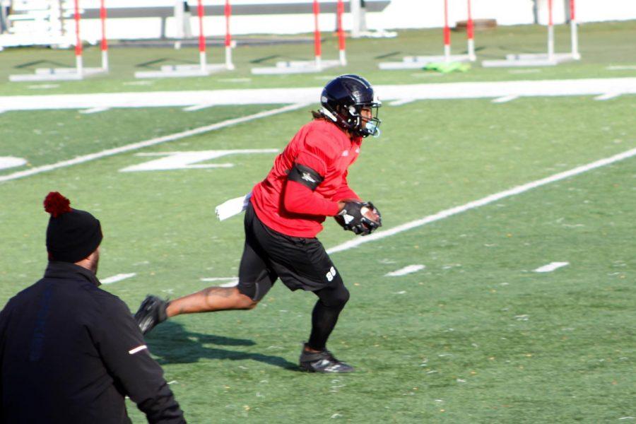 Redshirt senior tight end Daniel Crawford runs with the ball Oct. 16, during practice at Huskie Stadium.