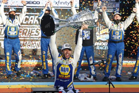 Chase Elliott holds up the season championship trophy as he celebrates with his race crew in Victory Lane after winning a NASCAR Cup Series auto race at Phoenix Raceway, Sunday, Nov. 8, 2020, in Avondale, Ariz.