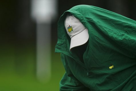Joe Mulholland puts on a rain jacket during a practice round at the Masters golf tournament Wednesday, Nov. 11, 2020, in Augusta, Ga.