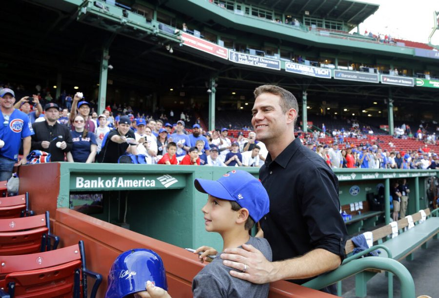 FILE - In this April 28, 2017, file photo, Theo Epstein, president of baseball operations for the Chicago Cubs, poses with a young fan prior to a baseball game between the Boston Red Sox and the Cubs at Fenway Park in Boston. Theo Epstein, who transformed the long-suffering Chicago Cubs and helped bring home a drought-busting championship in 2016, is stepping down after nine seasons as the club's president of baseball operations. The team announced Monday, Nov. 16, 2020, Epstein is leaving the organization, and general manager Jed Hoyer is being promoted to take his place.