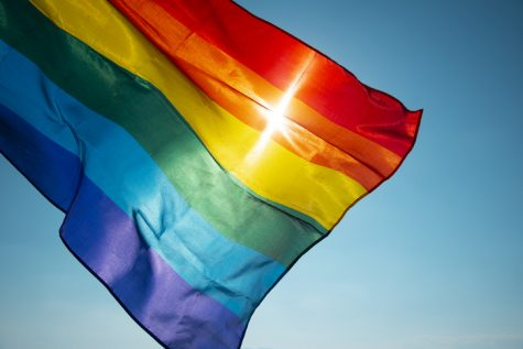 closeup of a rainbow flag waving on the blue sky, moved by the wind, with the sun in the background