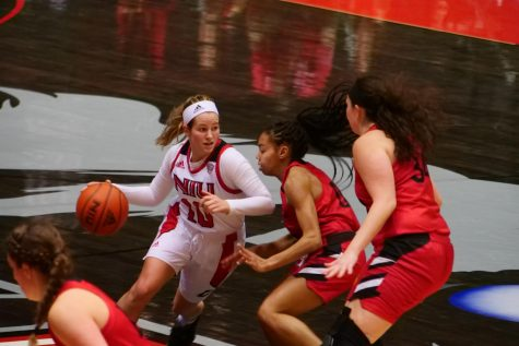 Sophomore guard Chelby Koker (left) drives past two defenders Nov. 25, during NIU