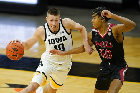 Iowa guard Joe Wieskamp drives past Northern Illinois guard Anthony Crump, right, during the first half of an NCAA college basketball game, Sunday, Dec. 13, 2020, in Iowa City, Iowa.