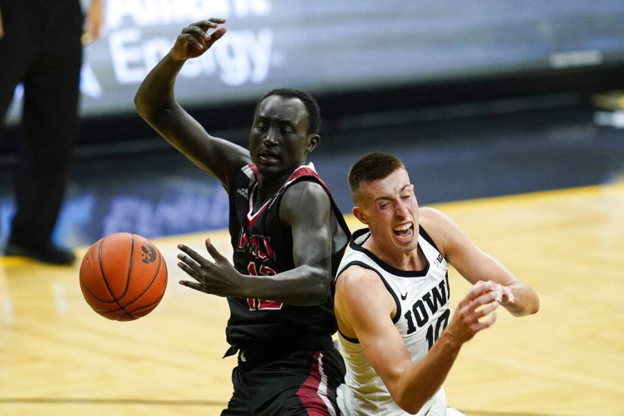 Northern Illinois junior forward Zool Kueth, left, fights for a rebound with Iowa junior guard Joe Wieskamp, right, during the first half of an NCAA college basketball game, Sunday, Dec. 13, 2020, in Iowa City, Iowa.