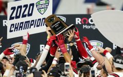 Ball State players reach for the trophy after defeating Buffalo in the Mid-American Conference championship NCAA college football game, Friday, Dec. 18, 2020, in Detroit.