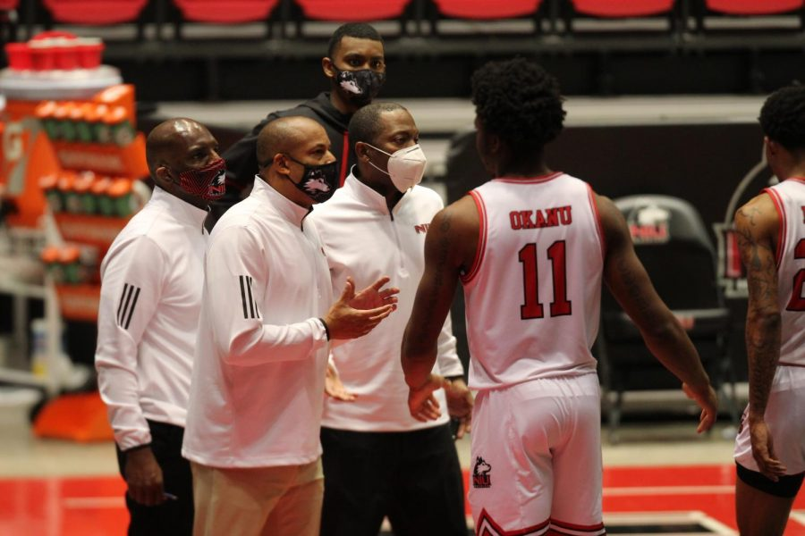 NIU Head Coach Mark Montgomery (second from the left) talks with junior forward Chinedu Kingsley Okanu (right) during a timeout Dec. 8, after Kingsley Okanu picked up a blocking foul late in NIU's 79-70 Loss to Ball State at the NIU Convocation Center in DeKalb.